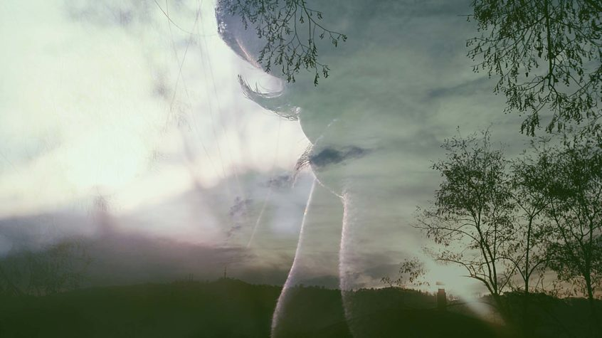 Double Exposure Human Face Against Landscape